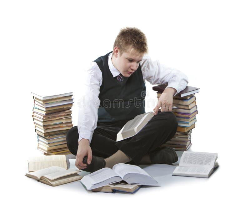 Skolpojken i en skolalikformig sitter på ett golv, nära till packar av böcker, med den öppnade boken i händer arkivbild