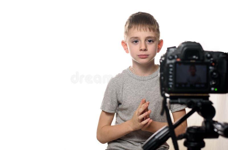 Skolpojken i koncentration förbereder sig för en intervju framme av en videokamera Ung video blogger Vit bakgrund fotografering för bildbyråer
