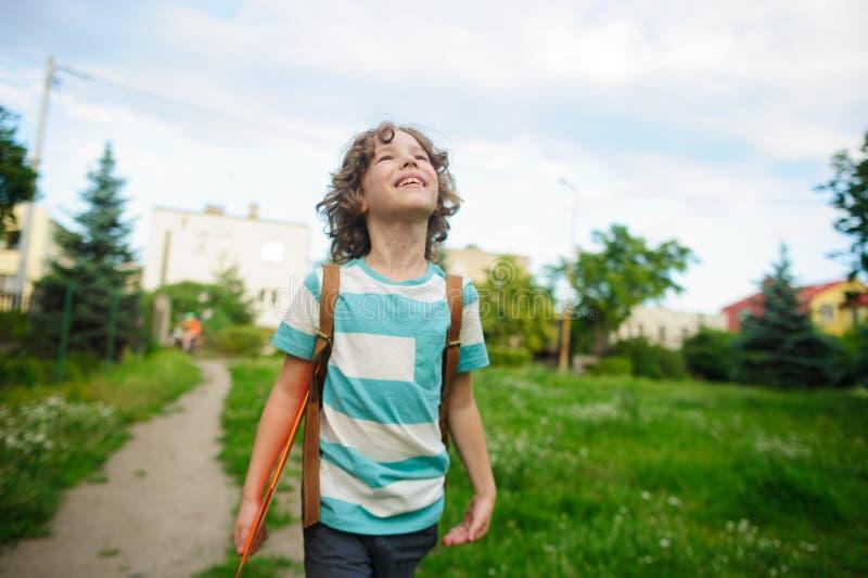 Skolpojken kommer tillbaka från skola i bra lynne fotografering för bildbyråer