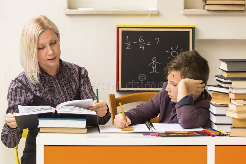 Skolpojken lär med läraren arkivfoto