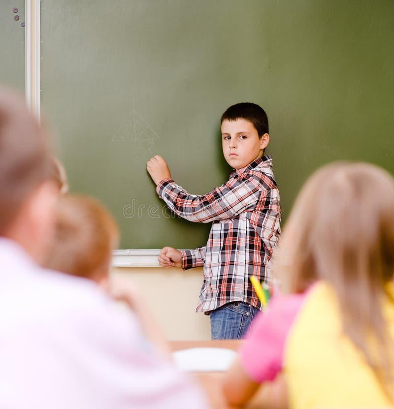 Skolpojken svarar frågor av lärare nära en skolförvaltning royaltyfri foto