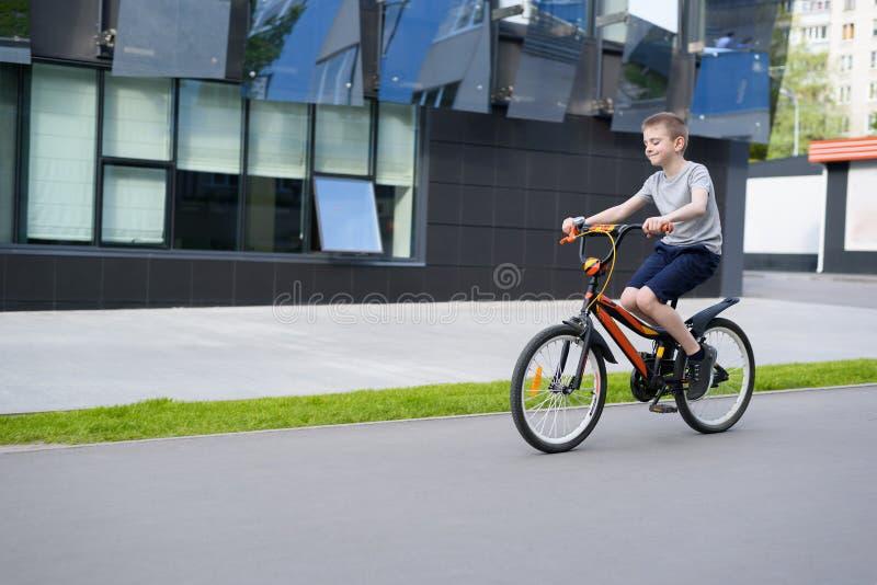 Skolpojkeritter en cykel lycklig din feriesommar f?r familj stads- bakgrund fotografering för bildbyråer