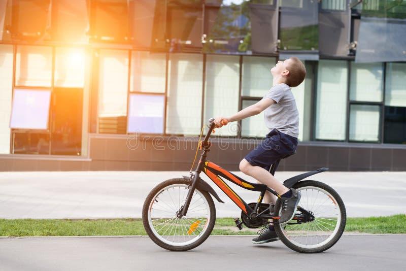 Skolpojkeritter en cykel lycklig din feriesommar f?r familj stads- bakgrund arkivbild