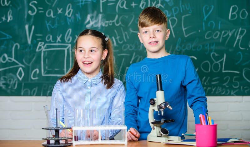 Skolutbildning Flickan och pojken meddelar experiment f?r stunduppf?randeskola Barn som tillsammans studerar klassrumet royaltyfri bild