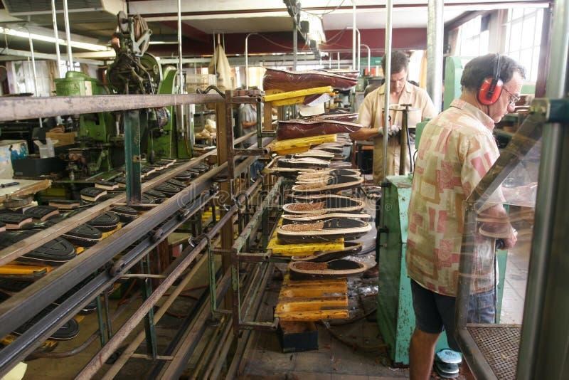 Skomakarearbetare på fabriken arkivbilder