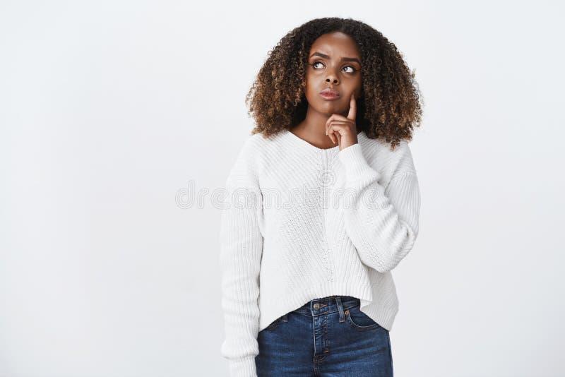 Skomplikowana dziewczyna ma wątpienia stoi rozważnego wzruszającego policzek z palcem marszczy brwi górnego lewego kąt i pat zdjęcia royalty free