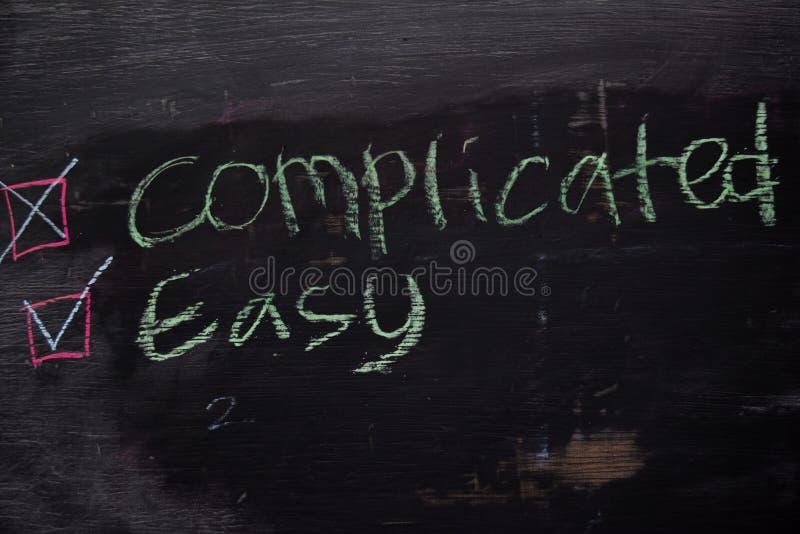 Skomplikowany lub Łatwy pisać z kolor kredy pojęciem na blackboard zdjęcia stock