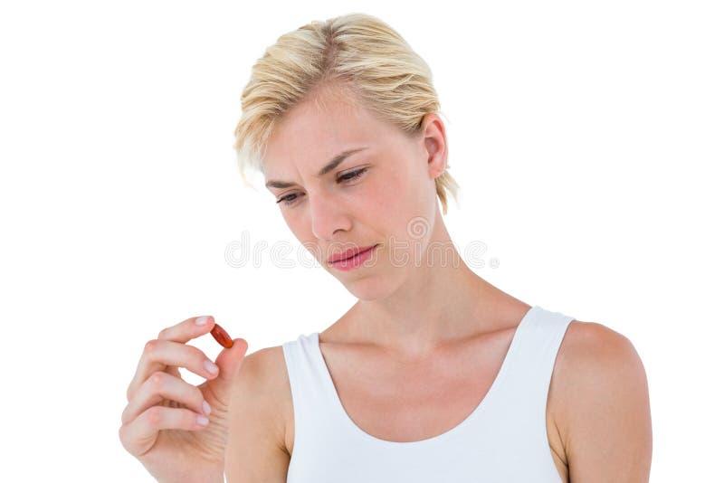 Skoncentrowana blondynki kobieta patrzeje czerwoną pigułkę fotografia stock