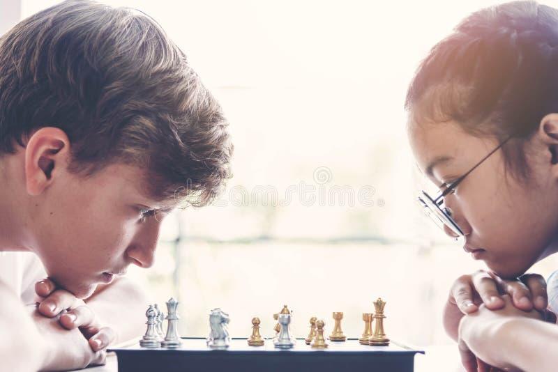 Skoncentrowana chłopiec i dziewczyna rozwija szachową strategię, bawić się grę planszową Dzieci myśleć, planujący poruszającego s obrazy royalty free