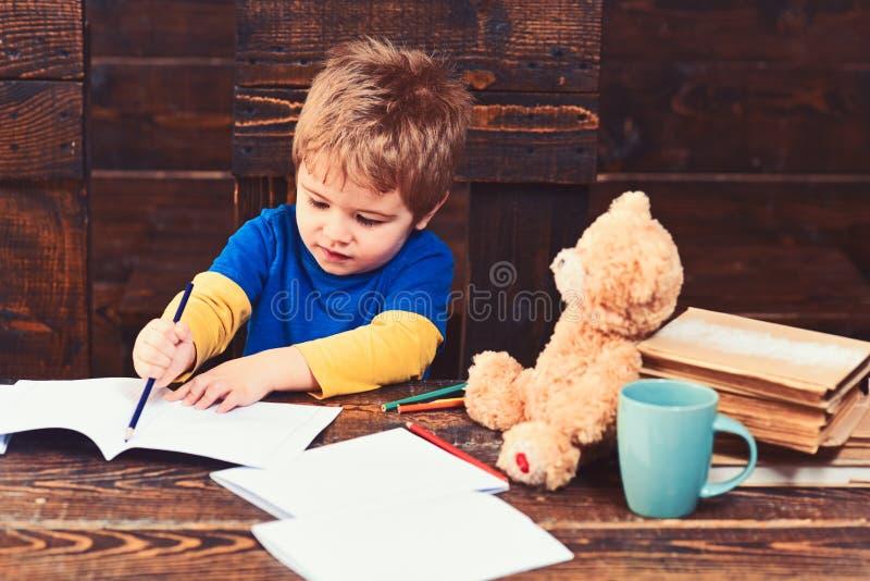 Skoncentrowana chłopiec rysunku linia z błękitnym ołówkiem Ruchliwie dzieciak pisze w ćwiczenie książce Uczeń na drewnianym panel obraz stock