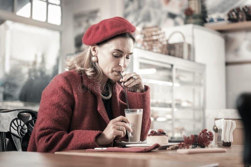 Skoncentrowana dojrza?a kobieta pije gor?c? czekolad? w kawiarni obraz royalty free