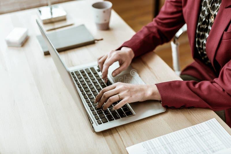 Skoncentrowana dorosła kobieta w biurowym stroju obsiadaniu przed laptopem obrazy royalty free