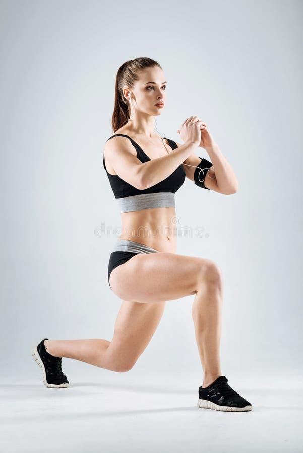 Skoncentrowana dziewczyna robi lunges na popielatym tle zdjęcie royalty free