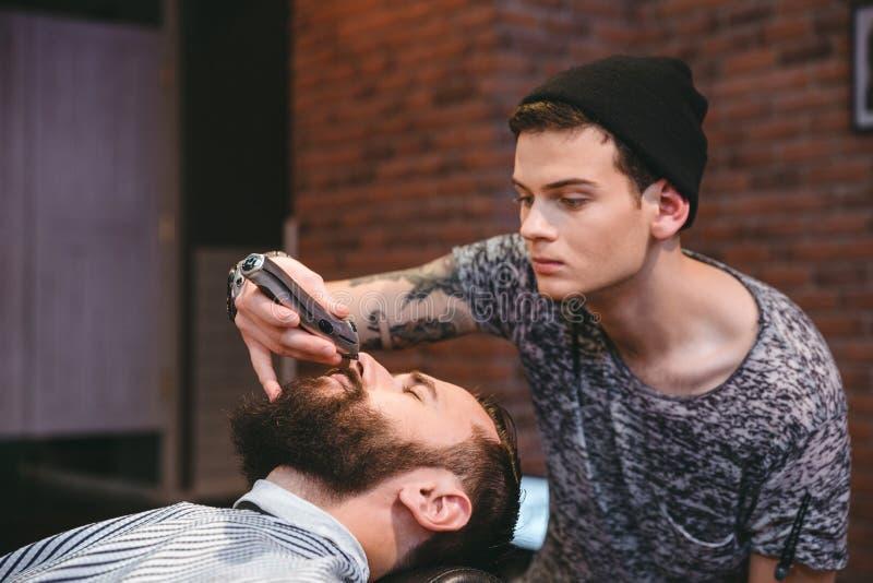Skoncentrowana fryzjera męskiego arymażu broda przystojny mężczyzna w zakładzie fryzjerskim zdjęcie royalty free