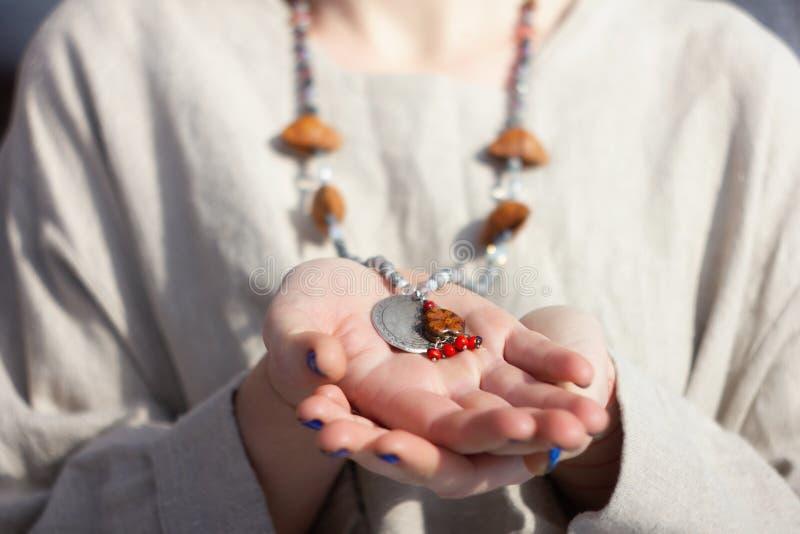 Skoncentrowana kobieta jest ubranym różanów koraliki z bliska fotografia stock