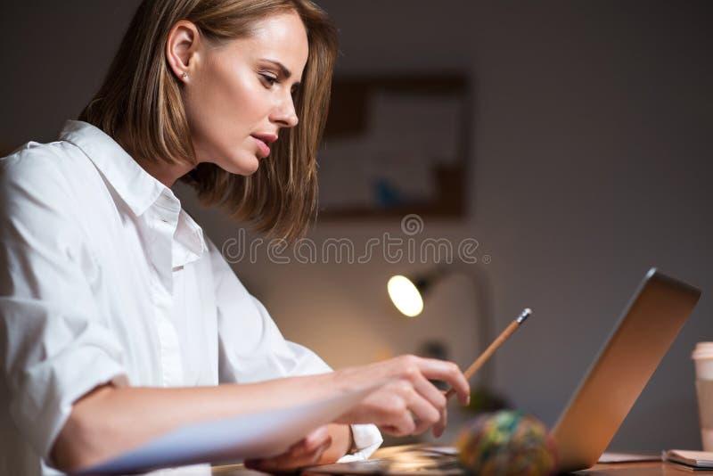 Skoncentrowana kobieta pracuje na laptopie fotografia stock