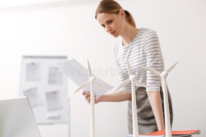 Skoncentrowana kobieta pracuje na silnika wiatrowego projekcie obraz royalty free
