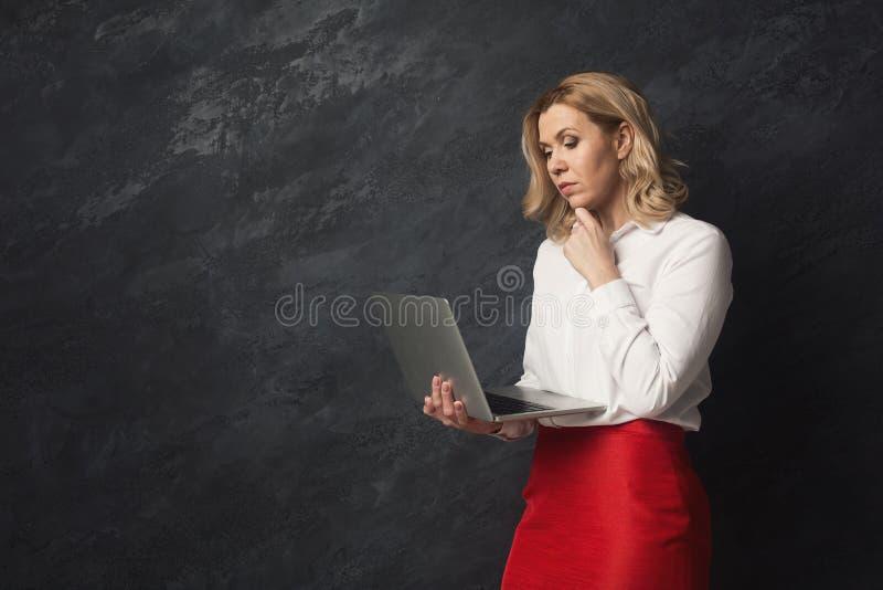 Skoncentrowana kobieta z laptopem na szarym tle obraz stock