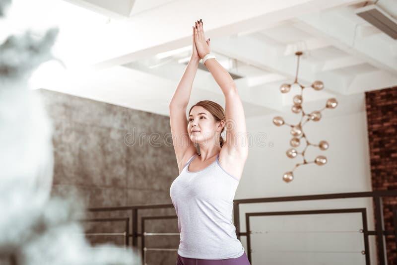 Skoncentrowana schludna kobieta podnosi ona z curvy postacią ręki zdjęcia stock