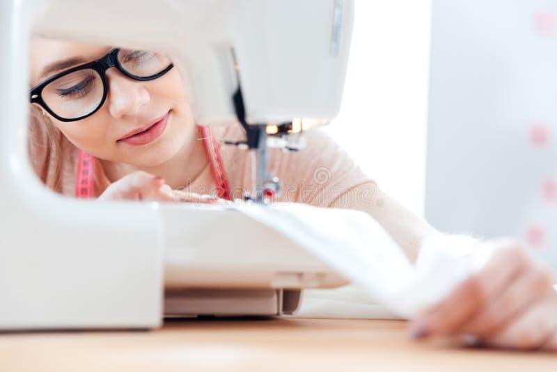 Skoncentrowana szwaczka przy pracą z sukienną tkaniną zdjęcie royalty free