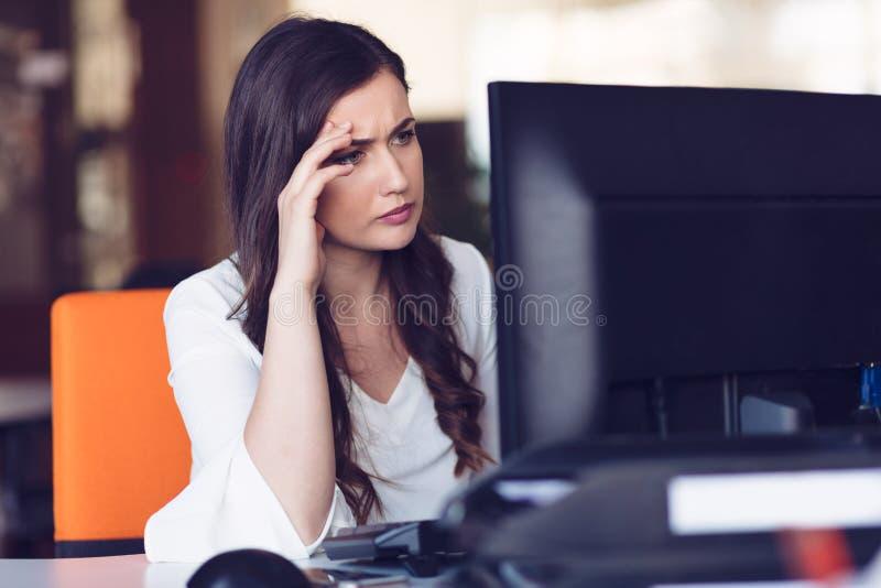Skoncentrowana w średnim wieku kobieta pracuje na jej komputerze Uruchomienia biura tło obrazy royalty free
