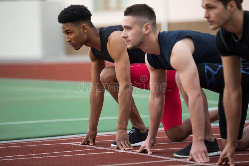 Skoncentrowana wieloetniczna atlety grupa przygotowywająca bieg obrazy royalty free
