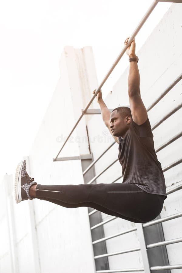 Skoncentrowane amerykanin afrykańskiego pochodzenia sportowa rozgrzewkowego w górę i rozciągania nogi na molu, ciągnienia w górę  zdjęcie stock