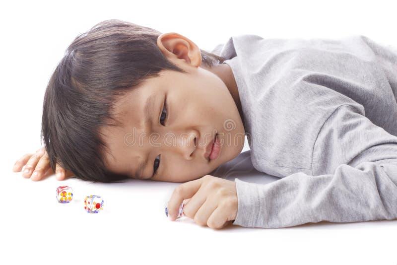 Skoncentrowane chłopiec sztuki dices na stole zdjęcie royalty free