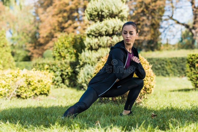 skoncentrowane młodej kobiety rozciągania nogi zdjęcie royalty free