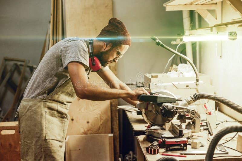 Skoncentrowanego rzemieślnika tnący drewno na workbench zdjęcie stock