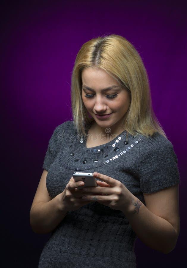 Skoncentrowanej blondynki mienia z włosami wzorcowy smartphone na czarnym tle zdjęcie stock