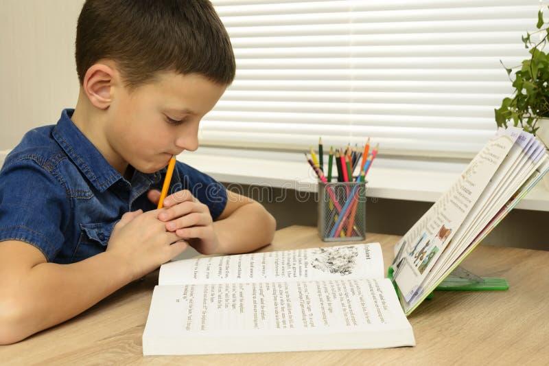 Skoncentrowanej chłopiec czytelnicza książka podczas gdy robić pracie domowej zdjęcia stock
