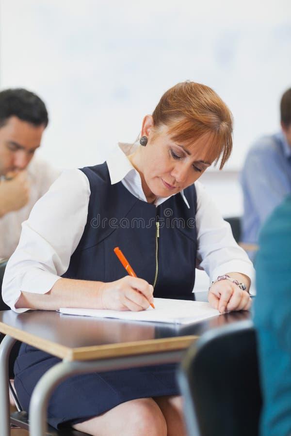 Skoncentrowanej kobiety dojrzały studencki obsiadanie w sala lekcyjnej fotografia stock