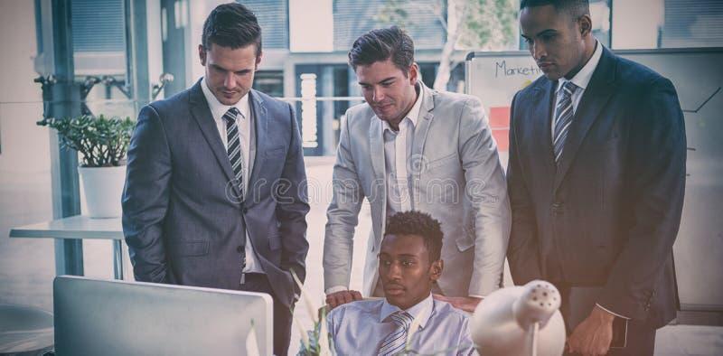 Skoncentrowani biznesmeni patrzeje komputer obraz stock