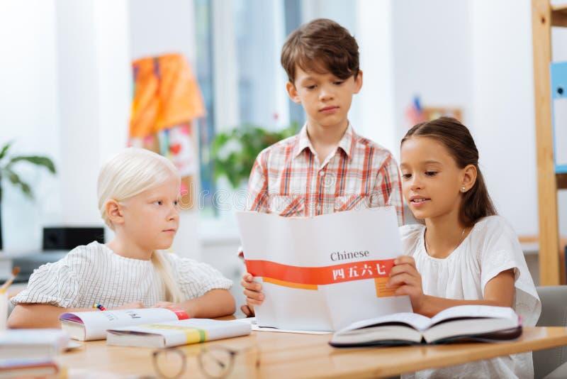 Skoncentrowani dzieci płaci uwagę na szczegółach w ćwiczeniu obraz royalty free