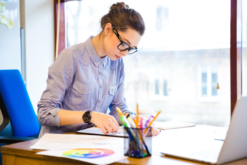 Skoncentrowani kobieta projektanta mody rysunku nakreślenia w biurze obraz royalty free