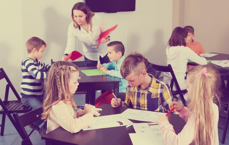 Skoncentrowani małe dzieci z nauczyciela rysunkiem w sala lekcyjnej obrazy stock