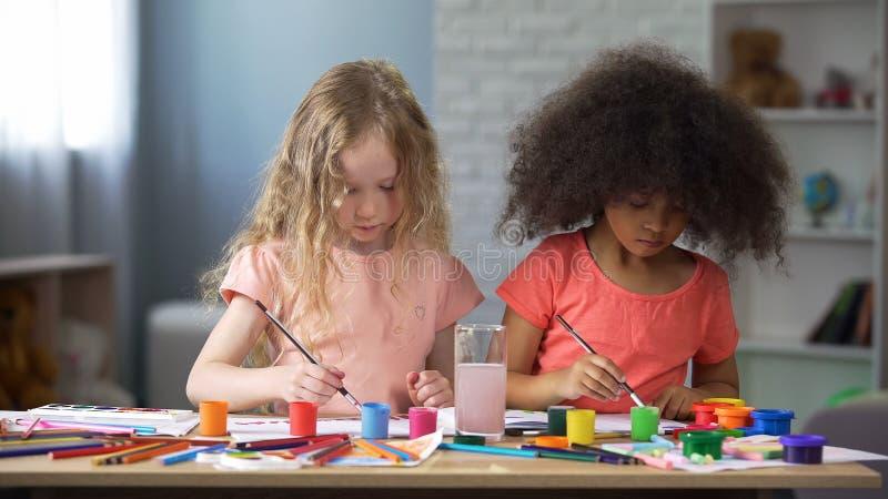 Skoncentrowani multiracial przyjaciele maluje przy szkołą artystyczną, preschool edukacja zdjęcia stock