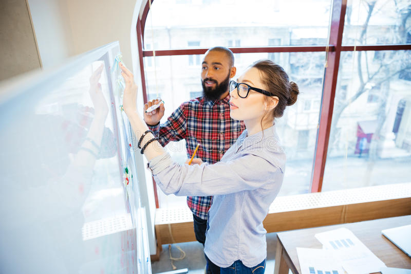 Skoncentrowani ucznie stoi i pisze na whiteboard w sala lekcyjnej obrazy stock