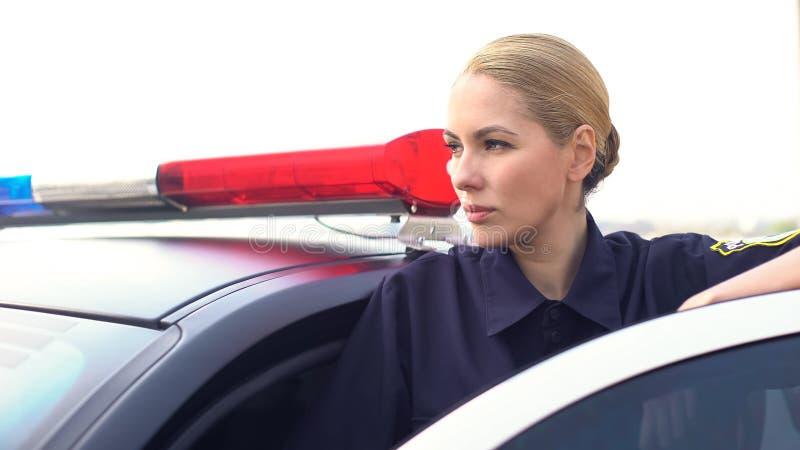 Skoncentrowany żeński oficera monitorowanie drogowa sytuacja stoi blisko samochodu policyjnego obrazy royalty free