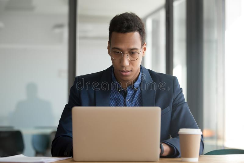 Skoncentrowany amerykanin afryka?skiego pochodzenia biznesmen pracuje przy laptopem w biurze fotografia royalty free