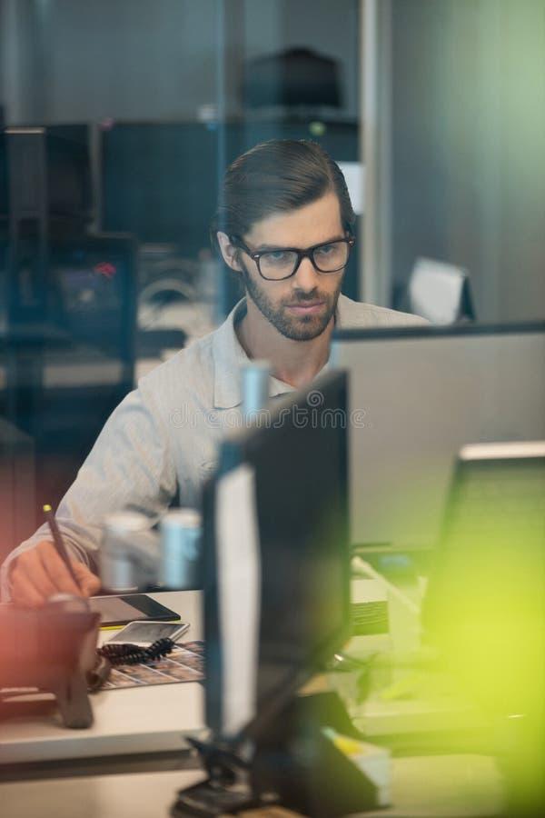 Skoncentrowany biznesmen pracuje na digitizer w biurze fotografia stock