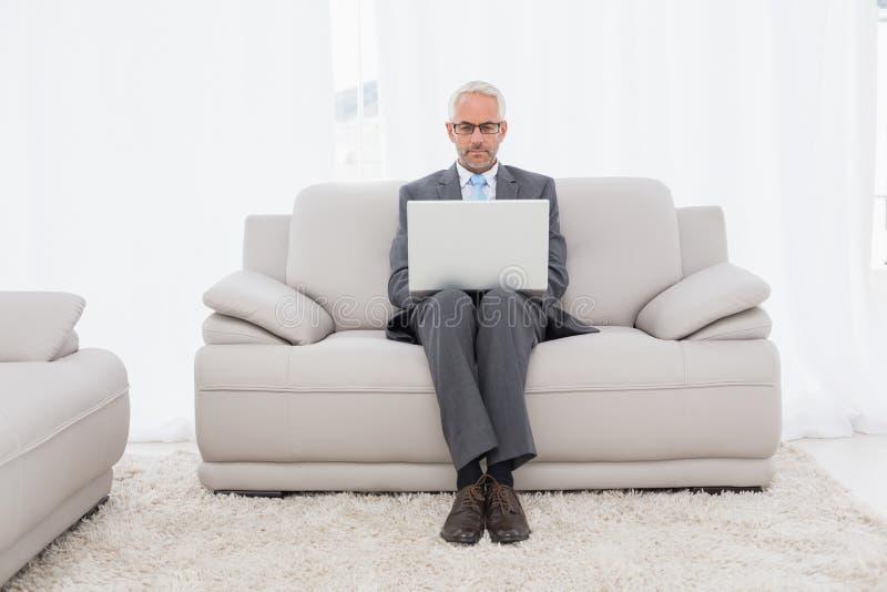 Skoncentrowany biznesmen używa laptop na kanapie w żywym pokoju fotografia stock