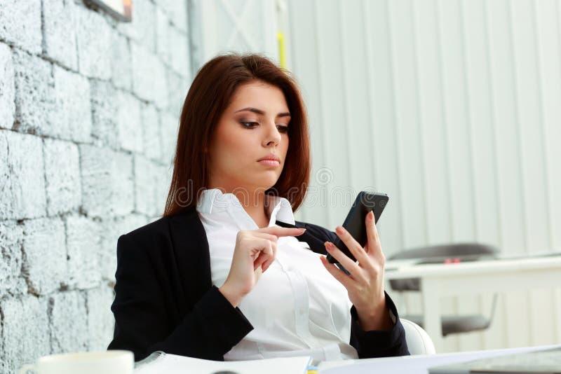 Skoncentrowany bizneswoman patrzeje ekran smartphone obrazy royalty free