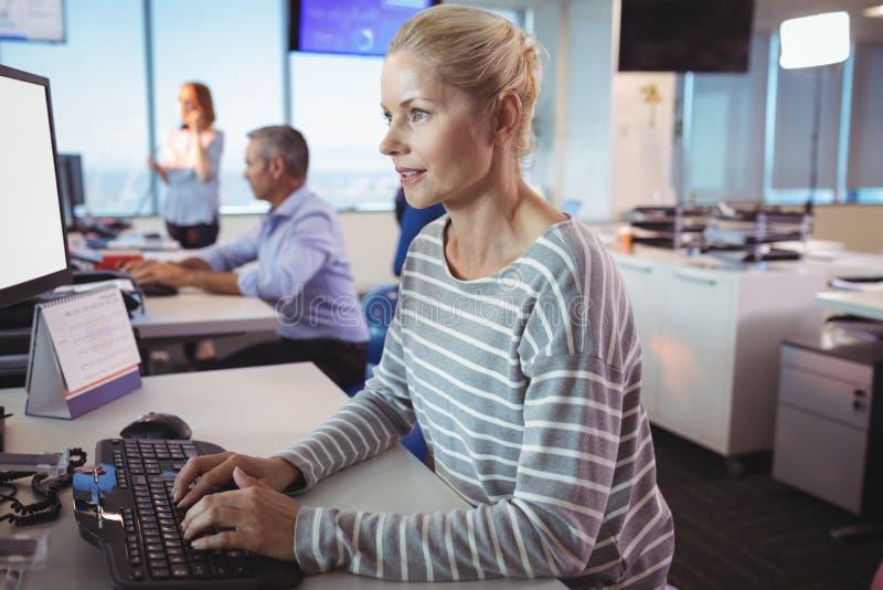 Skoncentrowany bizneswoman pisać na maszynie na klawiaturze przy biurem zdjęcie stock