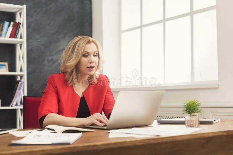 Skoncentrowany bizneswoman pracuje na laptopie przy biurem obrazy royalty free