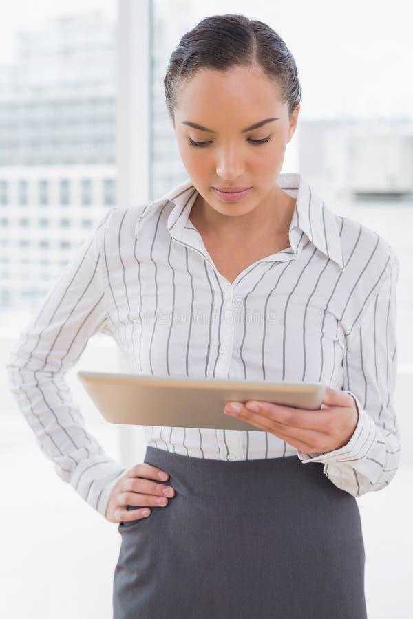 Skoncentrowany bizneswoman używa jej pastylka komputer osobistego fotografia stock