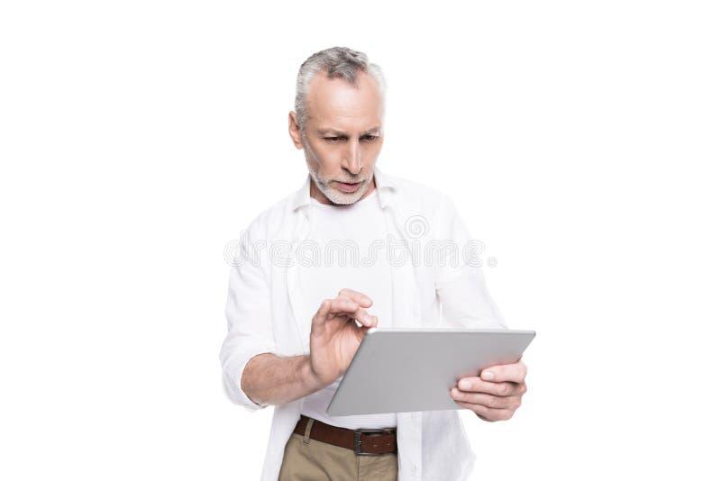 Skoncentrowany brodaty dorośleć mężczyzna używa cyfrową pastylkę obraz royalty free