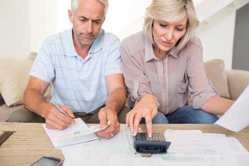 Skoncentrowany dorośleć pary z rachunkami i kalkulatora w domu zdjęcia royalty free