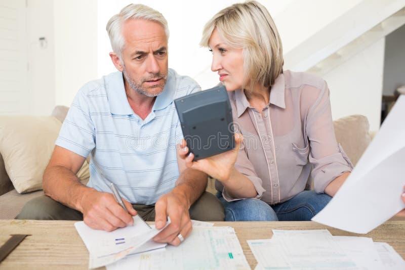 Skoncentrowany dorośleć pary z rachunkami i kalkulatora w domu obrazy stock